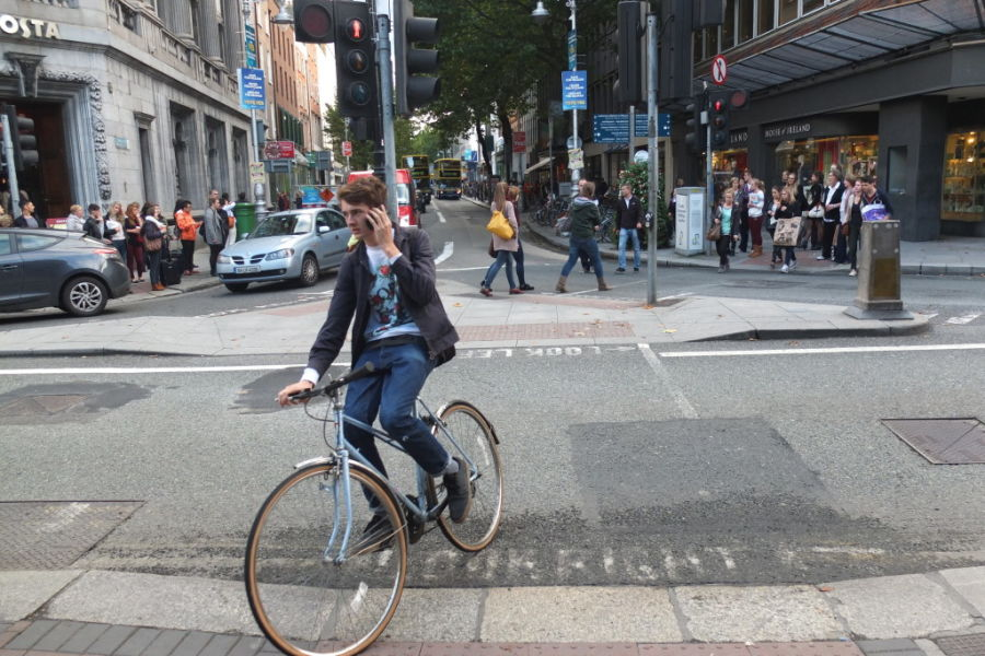 Dubin Ireland riding bicycle while on cell phone